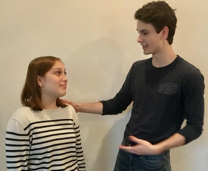 Two students acting out a role play. A tall student has his hand on the shoulder of a girl. He is reassuring her, but she looks skeptical.
