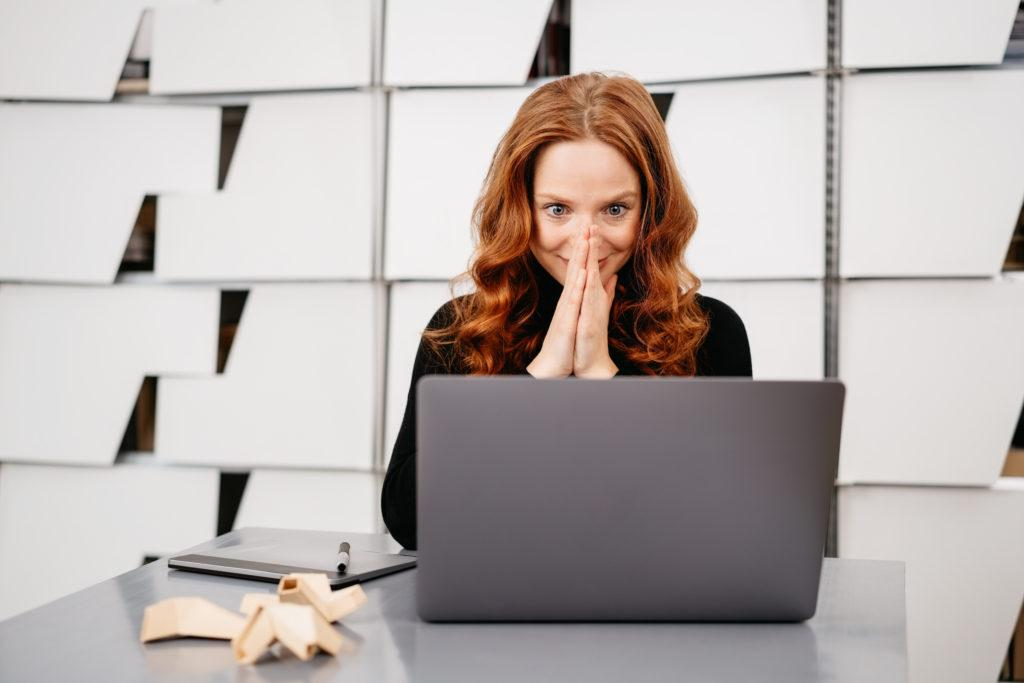 Excited young businesswoman looking at her laptop with a wide eyed look of anticipation and amazement as she sits at a table in a modern office