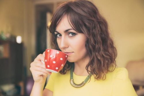 Close Up of Woman Drinking from Red Polka Dot Tea Mug and Looking at Camera