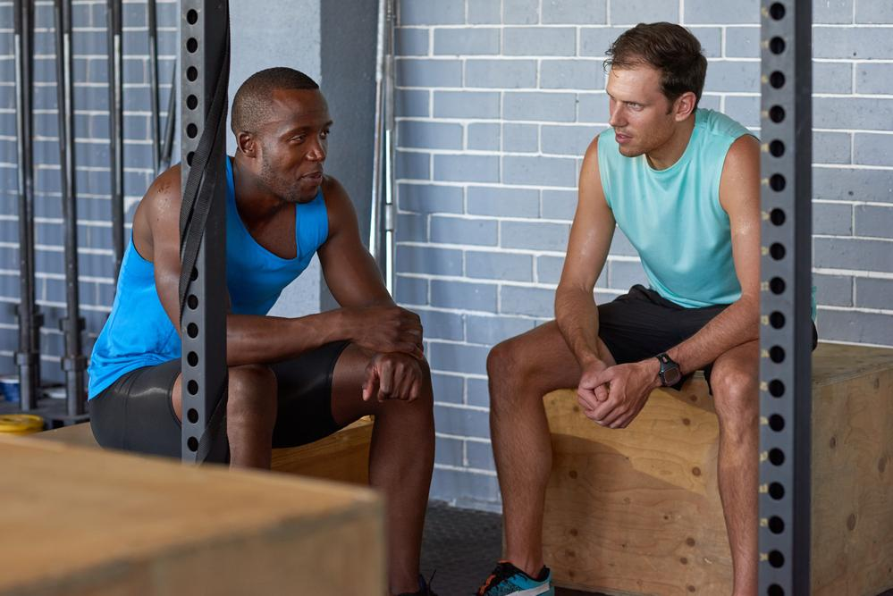 A black man and a white man sitting in the gym and talking