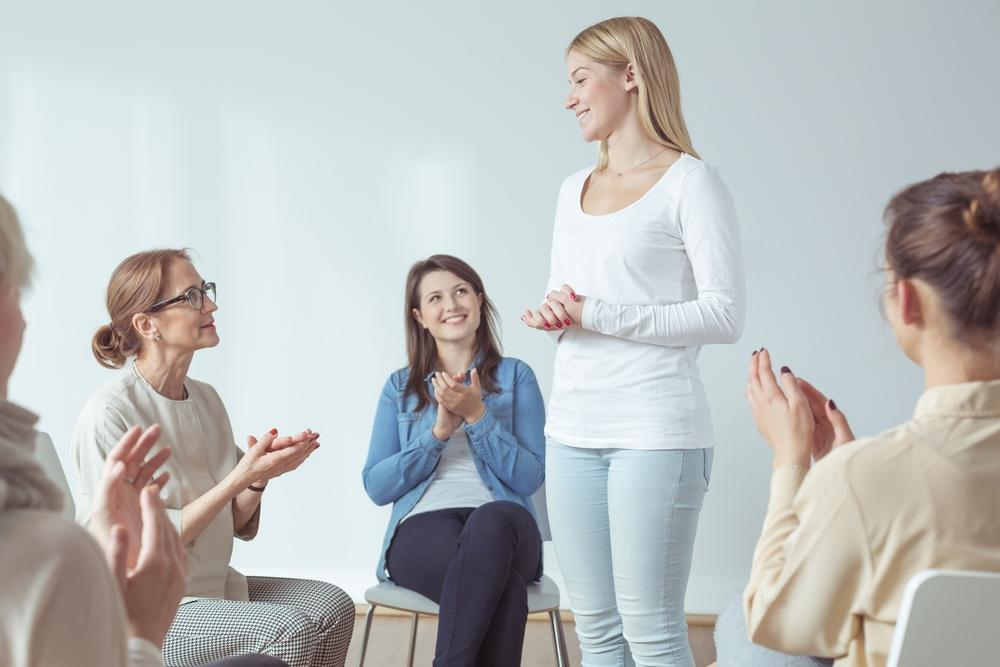 Four women sitting in a circle and clapping as a fifth woman stands and shares some achievement